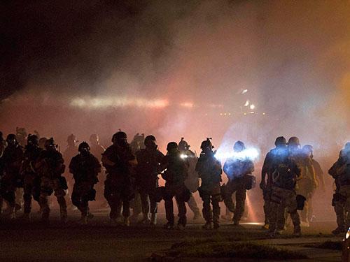 Cảnh sát chống bạo động dùng bom khói để giải tán người biểu tình ở TP Ferguson hôm 13-8Ảnh: Reuters