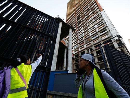 Cư dân rời khỏi tòa tháp David hôm 22-7 Ảnh: Reuters