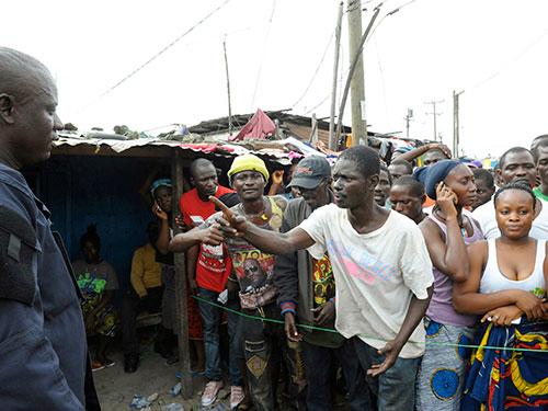 Những người dân bị cách ly tại khu ổ chuột West Point ở thủ đô Monrovia - Liberia để ngăn dịch Ebola lây lan Ảnh: Reuters