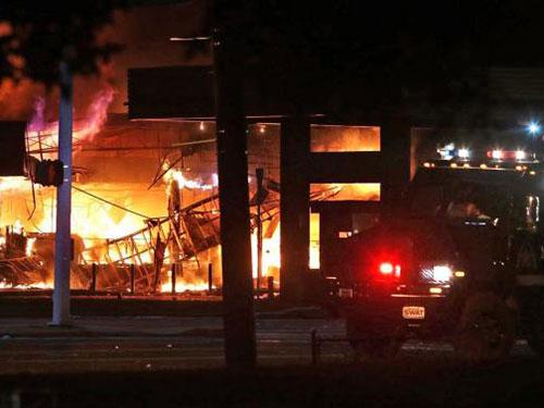 Một cửa hàng bị đốt phá ở Ferguson trong đêm 10-8 Ảnh: Reuters