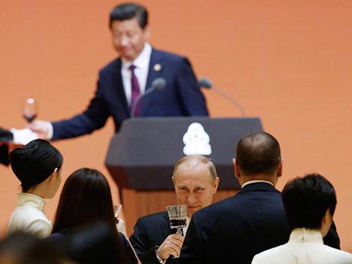 Tổng thống Nga Vladimir Putin và Chủ tịch Trung Quốc Tập Cận Bình (phía sau) tại Thượng Hải ngày 20-5 Ảnh: The New York Times