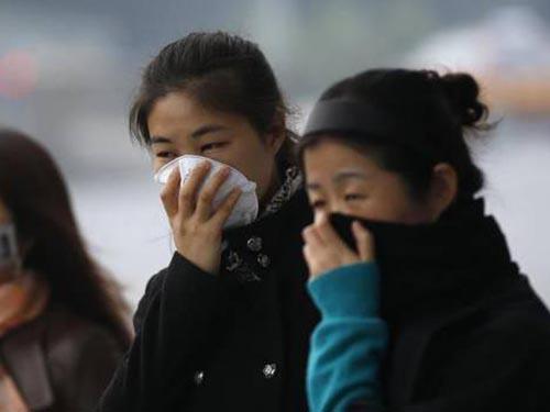 Một số người đeo khẩu trang chờ xe buýt trong một ngày khói bụi ở Bắc Kinh-Trung Quốc. Ảnh: Reuters