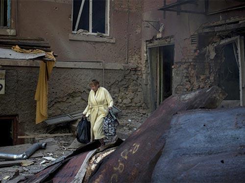 Một phụ nữ bên ngoài tòa nhà bị bom đạn ở Lugansk Ảnh: RIA NOVOSTI
