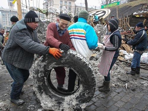 Phe đối lập dọn dẹp chướng ngại vật quanh tòa thị chính Kiev hôm 16-2Ảnh: EPA