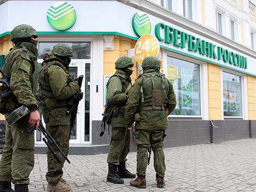 Các tay súng tuần tra trung tâm thủ phủ Symferopol của Crimea hôm 1-3 Ảnh: REUTERS