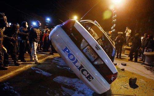 Người biểu tình ở Ferguson lật xe cảnh sát đêm 25-11  Ảnh: REUTERS
