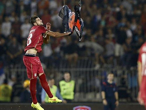Cầu thủ Stefan Mitrovic của Serbia kéo lá cờ xuống, dẫn đến trận ẩu đả Ảnh: REUTERS