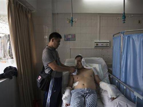 Anh Lý Kiến Tân bị thương nặng sau khi tố cáo hành vi sai phạm Ảnh: REUTERS