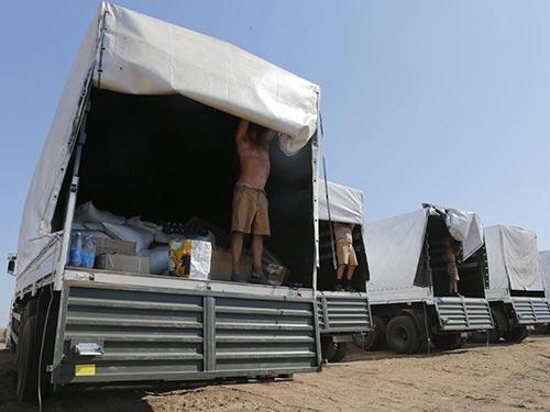 Các tài xế đoàn xe chở hàng cứu trợ của Nga mở cửa xe để phía Ukraine kiểm tra Ảnh: REUTERS