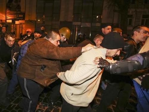 Nhân viên Bộ Nội vụ mặc thường phục bị người biểu tình giải đi hôm 21-2 Ảnh: REUTERS