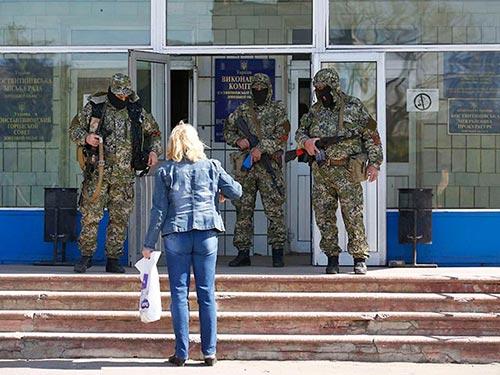 Những người có vũ trang canh gác trước tòa nhà Hội đồng TP Konstantinovka hôm 28-4 Ảnh: REUTERS