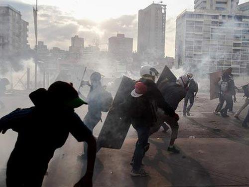 Một vụ đụng độ giữa người biểu tình chống chính phủ và lực lượng an ninh tại Caracas hôm 12-3 Ảnh: AP