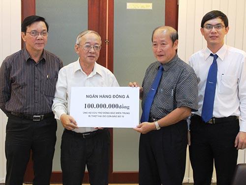 Đại diện Báo Người Lao Động tiếp nhận tiền ủng hộ đồng bào miền Trung bị lũ lụt của Ngân hàng Đông Á Ảnh: TRƯỜNG HOÀNG