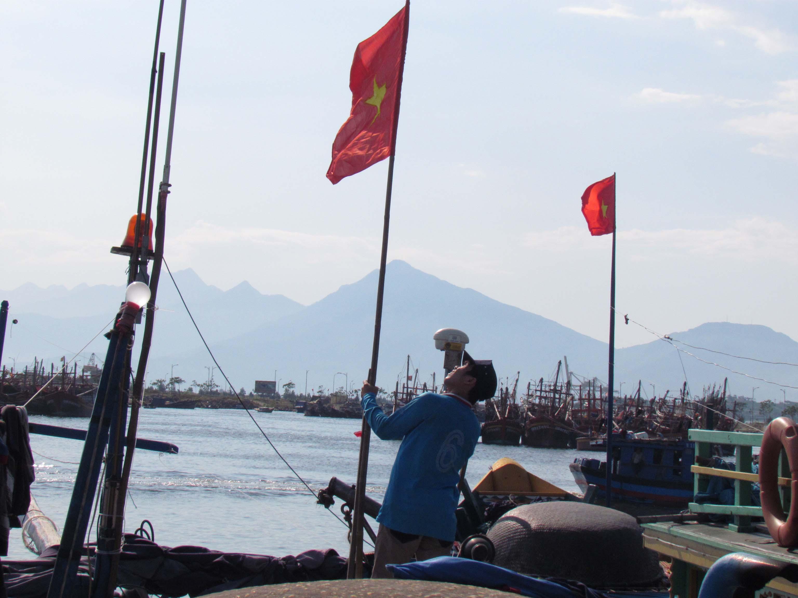 Ngư dân treo cờ Tổ quốc trên nóc tàu chuẩn bị ra khơi