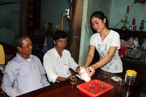 Nguyễn Thị Bích Phượng – cô gái đỗ thủ khoa khối C - rót nước mời ông nội và bà con chòm xóm trong nhà chật hẹp ở Thị trấn Trà Xuân, huyện Trà Bồng (Quảng Ngãi).