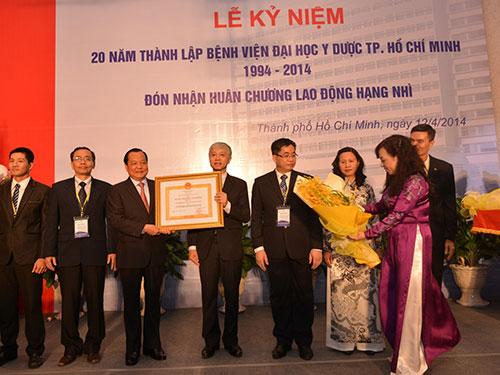 Ông Lê Thanh Hải - Ủy viên Bộ Chính trị, Bí thư Thành ủy TP HCM (thứ 3 từ trái qua) - trao Huân chương Lao động hạng Nhì cho Bệnh viện ĐH Y Dược TP HCM  Ảnh: CAO Trí