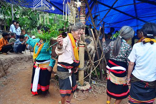 Phụ nữ Ca Dong mang gùi lá cỏ đá nhảy múa trong lễ đâm trâu.