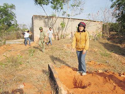 Chị Nguyễn Thị Hà khóc thảm thiết trước mộ con trai. Phía sau là ngôi nhà cấp 4 mới được xây dựng.