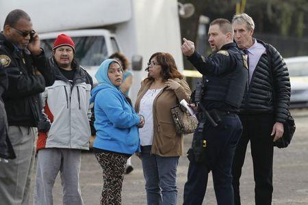 Phụ huynh cùng học sinh và các cảnh sát bên ngoài trường trung học. Ảnh: Reuters