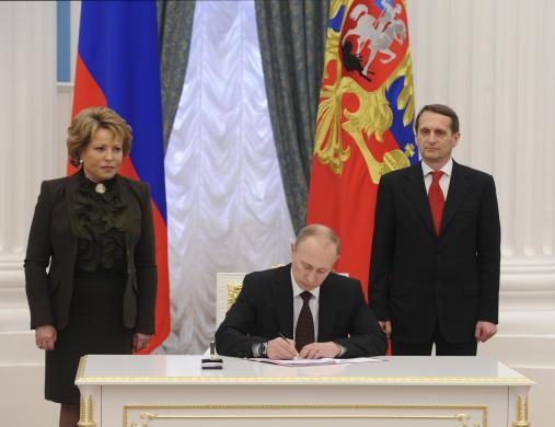 Tổng thống Putin ký luật sáp nhập Crimea tại Điện Kremlin ngày 21-3. Bên trái là Chủ tịch Thượng viện Valentina Matviyenko và bên phải là Chủ tịch Hạ viện Sergei Naryshkin. Ảnh: Reuters