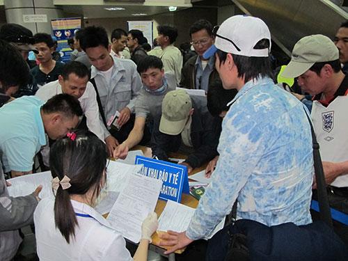 Hành khách đến từ vùng có dịch khai báo y tế tại sân bay Nội Bài khi nhập cảnh. Ảnh: D.Thu