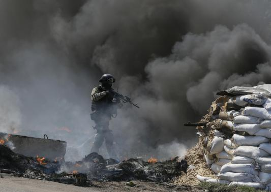 Binh sĩ Ukraine tiến gần một chốt chặn của phe ly khai gần Slavyansk hôm 24-4. Ảnh: Reuters