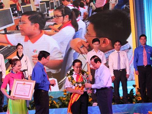 Bí thư Thành ủy TP HCM Lê Thanh Hải (bìa phải) trao danh hiệu Công dân trẻ tiêu biểu cho em Nguyễn Dương Kim Hảo, học sinh Trường THCS Nguyễn Gia Thiều, quận Tân Bình