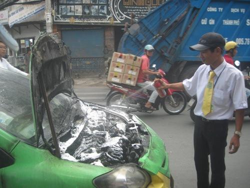 Tài xế xe dùng bình chữa cháy mini xịt những chỗ còn nóng, có nguy cơ cháy trở lại