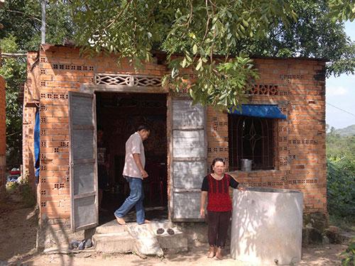 Chị Nguyễn Thị Cẩm trước căn nhà chênh vênh bên bờ sông Dinh Ảnh: Sĩ Nhân
