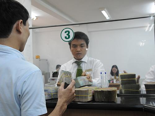Theo NFSC, tổng tài sản của hệ thống ngân hàng năm 2013 đã tăng 15%. Trong ảnh: Khách hàng giao dịch tại một ngân hàng ở TP HCM Ảnh: HỒNG THÚY