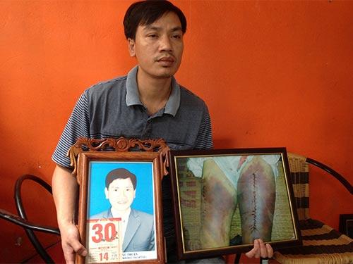 Người thân cầm ảnh ông Nguyễn Mậu Thuận tại phiên tòa sơ thẩm Ảnh: ĐỖ DU