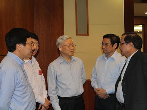 Tổng Bí thư Nguyễn Phú Trọng trao đổi với các đại biểu bên lề hội nghị Ảnh: NHẬT BẮC