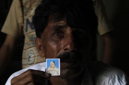 Muhammed Iqbal cầm hình vợ mới cưới đã chết. Ảnh: Reuters