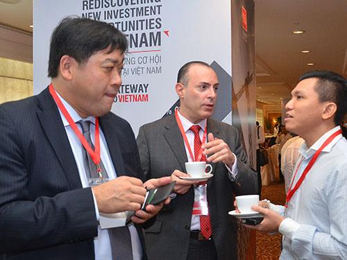 Các nhà đầu tư trao đổi cơ hội kinh doanh ngoài hành lang hội nghị Ảnh: Tấn Thạnh