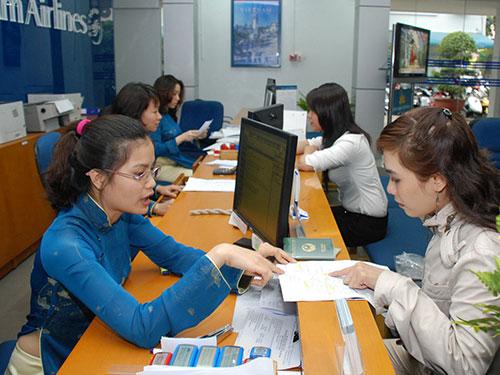 Hành khách mua vé máy bay tại một phòng vé của Vietnam Airlines Ảnh: TẤN THẠNH