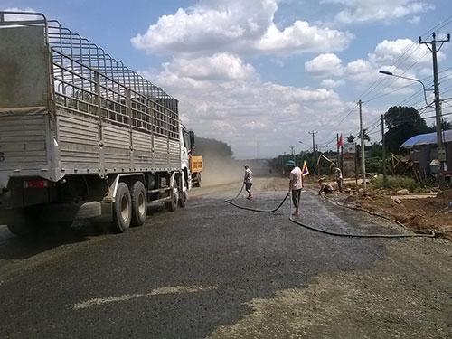 Người dân ở thị trấn Chư Sê, huyện Chư Sê, tỉnh Gia Lai phun nước ra đường để bớt bụi Ảnh: HOÀNG THANH