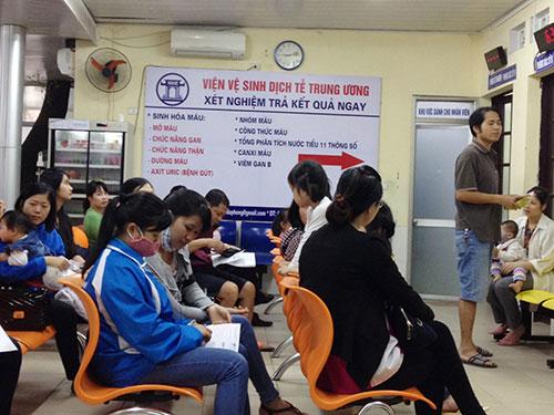 Các bậc phụ huynh đưa con em đi khám sàng lọc, tư vấn trước khi tiêm vắc-xin ở Hà Nội