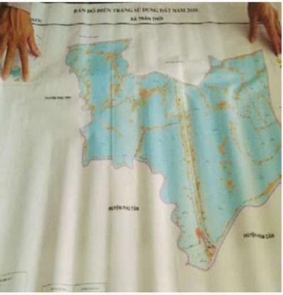 Bảng thông tin đặt trong nhà để xe ở tỉnh Vĩnh Long (ảnh trên) và cán bộ địa phương cho nhóm nghiên cứu xem bản đồ tại Cà Mau Ảnh: NHÓM NGHIÊN CỨU CỦA NGÂN HÀNG THẾ GIỚI