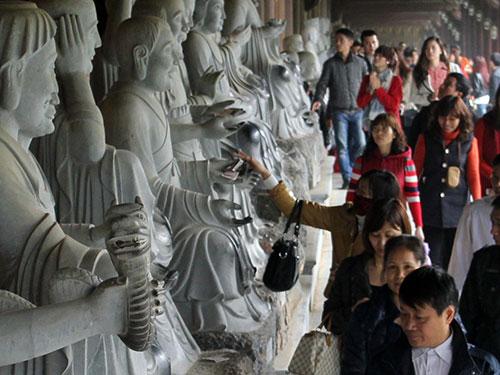 Nhét tiền vào tượng Phật ở chùa Bái Đình để cầu tài lộc