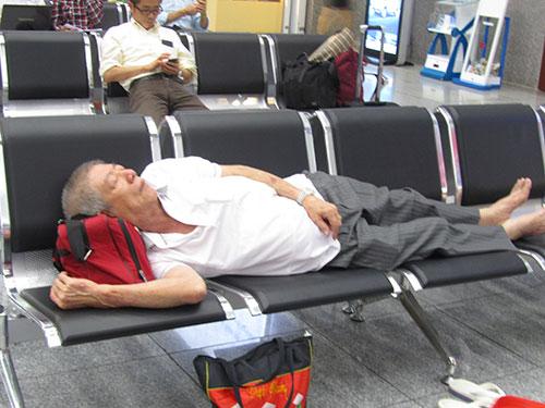 Một hành khách mệt mỏi nằm ngủ tại sân bay quốc tế Đà Nẵng tối 27-3 do chuyến bay bị hoãn Ảnh: THỦY TIÊN