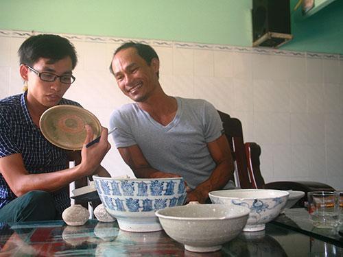 Ông Đinh Tấn Tàu (bìa phải) giới thiệu các cổ vật mình vớt được Ảnh: TRẦN THƯỜNG