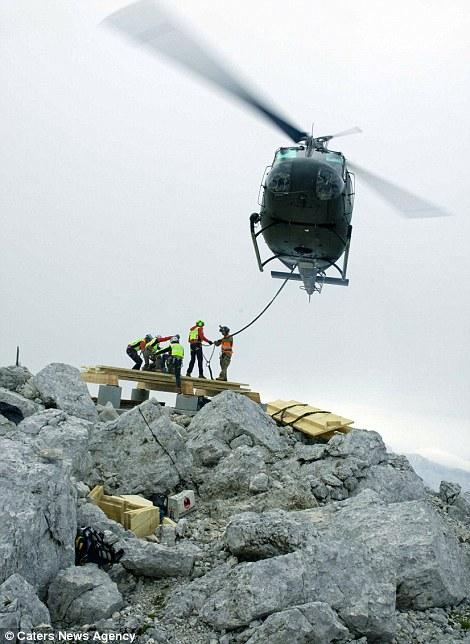 Trực thăng vận chuyển gỗ và thép lên đỉnh núi cao 2.530 m. Ảnh: Caters News Agency