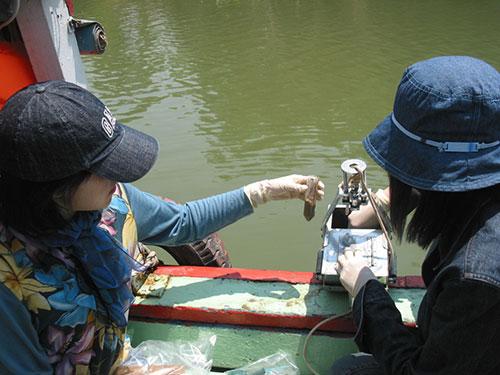Lấy nước sông Sài Gòn phục vụ nghiên cứu bảo vệ môi trường. (Ảnh do Chi cục Bảo vệ Môi trường TP HCM cung cấp)