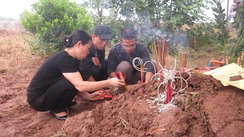 Anh Nguyễn Hữu Huy (giữa), chồng nạn nhân, cùng những người thân thắp hương trên mộ chị Huyền