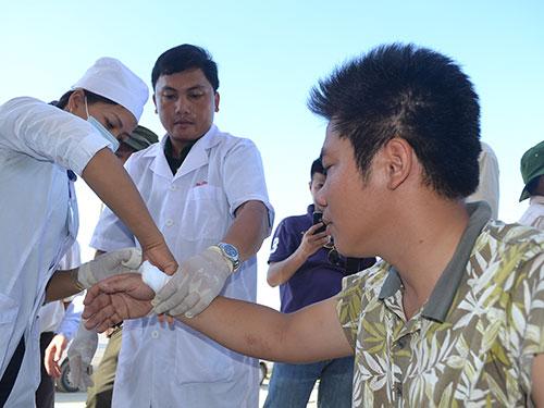 Nhân viên y tế băng bó vết thương cho ngư dân Nguyễn Huỳnh Bá Kiên Ảnh: QUỲNH NHƯ