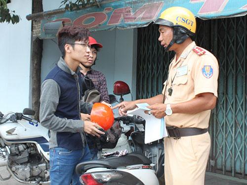 CSGT TP HCM hướng dẫn người dân nên đội mũ bảo hiểm đạt chất lượng khi tham gia giao thông Ảnh: THÀNH ĐỒNG