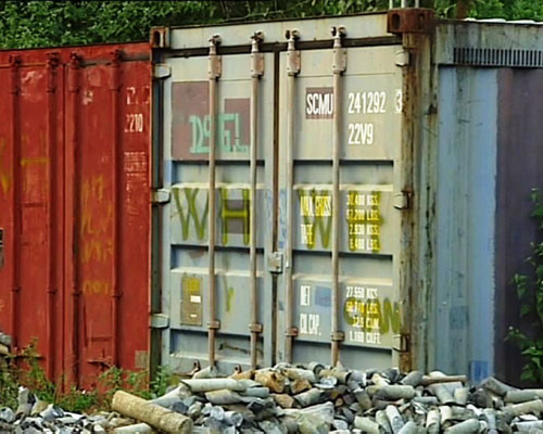 Các container chứa hóa chất vẫn bỏ ngoài trời và không có người trông coi Ảnh: PHẠM TRỌNG