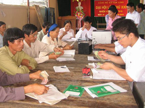 Hộ cận nghèo ở Tuyên Quang nhận vốn vay của NHCSXH tại điểm giao dịch xã. (Ảnh: website NHCSXH)