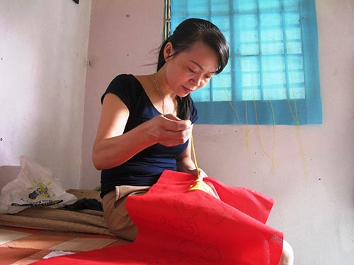 Chị Nguyễn Thị Tuyên đang thêu tranh làm quà Tết cho gia đình Ảnh: HỒNG NHUNG