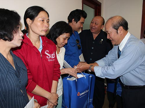 Ông Nguyễn Thanh Hùng, Phó Bí thư Thường trực Đảng ủy Ngân hàng Đông Á, trao tiền hỗ trợ từ chương trình cho công nhân khó khăn Ảnh: THANH NGA